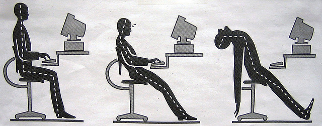 sitting at computer desk with poor posture