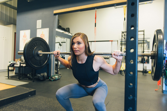 woman doing barbell back squat