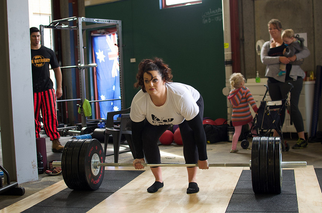 female weightlifter deadlifting barbell