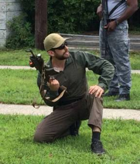Greg Mihovich crouching with rifle