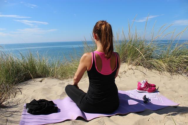 woman on yoga mat at beach